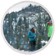 Couple Standing By A Campfire Round Beach Towel