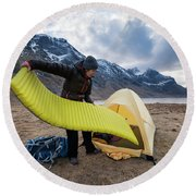 Female Hiker Sets Up Tent On Wild Round Beach Towel