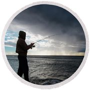 Fisherman Fishing While Storm Blows Round Beach Towel
