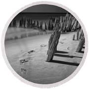 Footprints In The Sand Among The Pilings Round Beach Towel