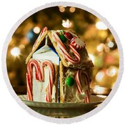 Gingerbread House Against A Background Of Christmas Tree Lights Round Beach Towel