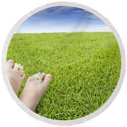 Girls Feet On Grass With Flowers Round Beach Towel