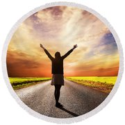 Happy Woman Standing On Long Road At Sunset Round Beach Towel