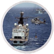 Hms Cornwall Is Pictured Receiving Stores By Merlin Helicopter  Round Beach Towel