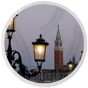 Lampposts Lit Up At Dusk With Building Round Beach Towel