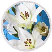 Lilies Against Blue Wall Round Beach Towel