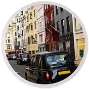London Taxi On Shopping Street Round Beach Towel