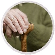 Old Hands Of A Senior On Walking Stick Round Beach Towel