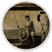 old sailor A vintage processed photo of a sailor sitted behind the rudder in Mediterranean sailing Round Beach Towel