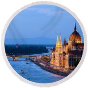 Parliament Building In Budapest At Evening Round Beach Towel