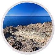 rocky coast in San Pietro island Round Beach Towel
