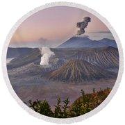 sunrise at vulcano Bromo with sea of sand vulcano Semeru with eruption Java Indonesia Round Beach Towel