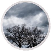 Two Trees Beneath A Dark Cloudy Sky Round Beach Towel