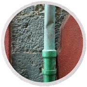 Vertical Drainpipe Against Colorful Round Beach Towel