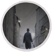 Victorian Man In Top Hat On A Cobbled Road At Night Round Beach Towel
