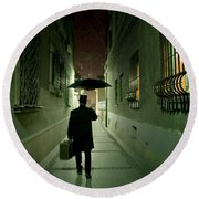 Victorian Man With Top Hat Carrying A Suitcase And Umbrella Walking In The Narrow Street At Night Round Beach Towel