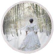 Victorian Woman Running Through A Winter Woodland With Fallen Sn Round Beach Towel