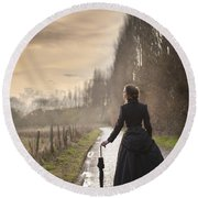 Victorian Woman Walking On A Cobbled Avenue At Sunset Round Beach Towel