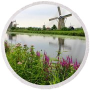 Windmills Of Kinderdijk With Wildflowers Round Beach Towel by Carol Groenen