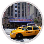 Yellow Cabs Pass In Front Of Radio City Music Hall Round Beach Towel