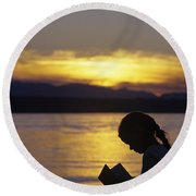 Young Girl Silhouetted Reading A Book On The Beach At Sunset Round Beach Towel