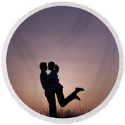 Young Lovers Embracing At Sunset Round Beach Towel