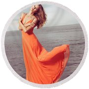 Young Woman In Orange Dress Flying In The Wind At Sea Shore Round Beach Towel by Oleksiy Maksymenko