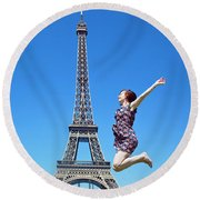 Young Woman Jumping Against Eiffel Tower Round Beach Towel