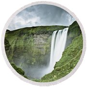A Waterfall Over A Grassy Cliff Round Beach Towel