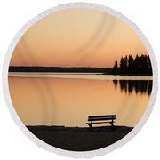 A Bench Silhouetted At Sunset Near The Round Beach Towel