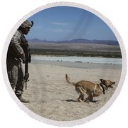 A Dog Handler Conducts Improvised Round Beach Towel by Stocktrek Images