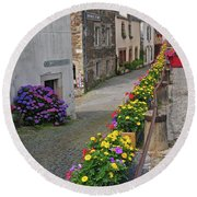 A Line Of Flowers In A French Village Round Beach Towel