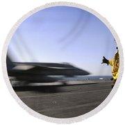 A Sailor Ensures An Fa-18c Hornet Round Beach Towel by Stocktrek Images