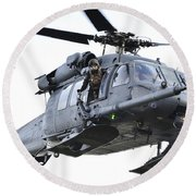 An Hh-60g Pavehawk Helicopter In Flight Round Beach Towel