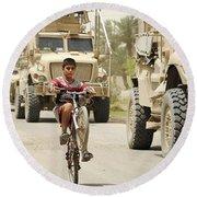 An Iraqi Boy Rides His Bike Past A U.s Round Beach Towel by Stocktrek Images