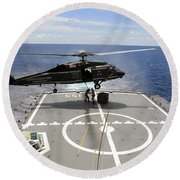 An Sh-60f Sea Hawk Helicopter Lowers Round Beach Towel