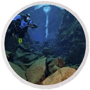 Dry Suit Divers In Gin Clear Waters Round Beach Towel