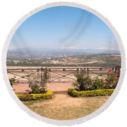 Fence And Garden Overlooking A Beautiful Vista Of Valley And Snow-capped Mountains Round Beach Towel
