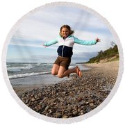 Girl Jumping At Lake Superior Shore Round Beach Towel