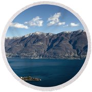 lake with Brissago islands and snow-capped mountain Round Beach Towel