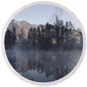 Mountain And Trees Reflected In A Foggy Lake Round Beach Towel