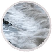 playing with waves 3 - Mediterranean sea foam playing with black stones in cala mesquida - menorca Round Beach Towel
