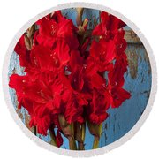 Red Glads Against Blue Wall Round Beach Towel