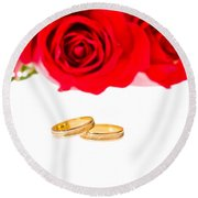 Red Roses And Wedding Rings Over White Round Beach Towel