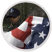 Soldier Unfurls A New Flag For Posting Round Beach Towel by Stocktrek Images