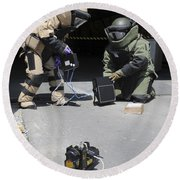 Soldiers Dressed In Bomb Suits Examine Round Beach Towel