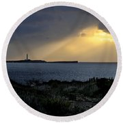 storm light - A morning light iluminates lighthouse through clouds in an amazing landscape Round Beach Towel