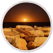 The Moon Rising Behind Rocks Lit Round Beach Towel