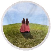 Two Girls In Vintage Dresses Walking Up Grassy Hill Round Beach Towel