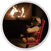Old Teddy Bear Sitting Front Of The Fireplace In A Cold Night Round Beach Towel